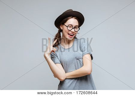 Happy Female nerd in black hat and eyeglasses which showing peace sign and winks