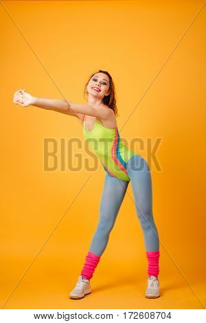 Full length of smiling young sportswoman standing and doing exercises over yellow background