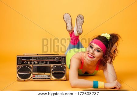Smiling beautiful young fitness woman lying near retro boombox over yellow background
