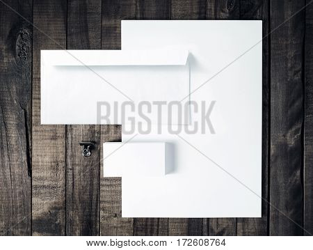 Blank stationery and corporate identity template Photo of blank letterhead business cards and envelope on vintage wooden table background. Responsive design mock up. Top view.