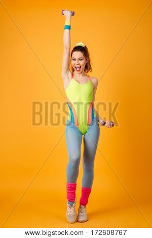 Full length of happy young woman athlete standing and training with dumbbells over yellow background