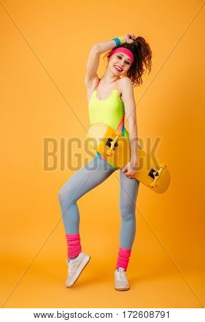 Full length of cheerful young sportswoman standing and holding skateboard over yellow background