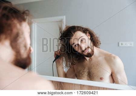 Attractive young man drying hair with hairdryer at home