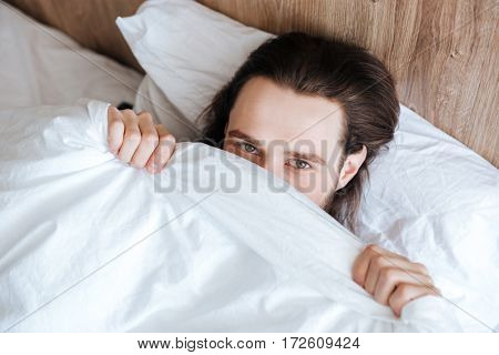 Handsome shy young man hiding his face under white coverlet in bed