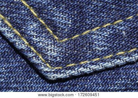 Blue denim material background with seam.  Textile clothing cotton jeans texture fabric macro closeup in studio.