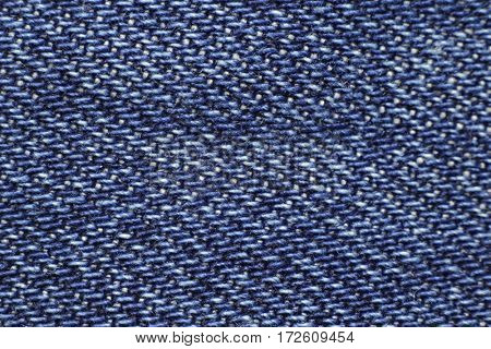 Blue jeans structure and texture for background close up in studio. Macro photo of new denim trousers. Cotton fabric picture.