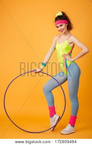 Cheerful young fitness woman working out and holding hula hoop over yellow background