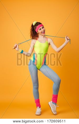 Happy playful young woman athlete holding jumping rope and winking over yellow background