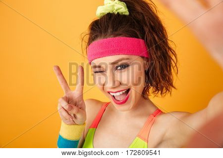Smiling young fitness woman taking selfie, winking and showing peace sign over yellow background