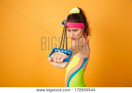 Concentrated young sportswoman standing and doing exercises with expander over yellow background