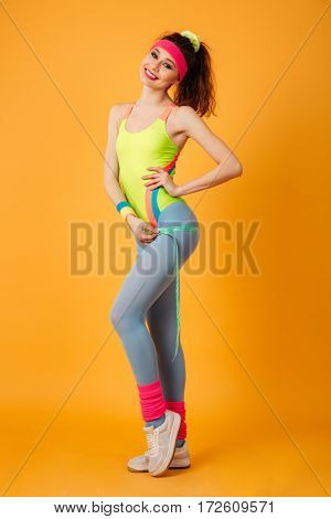 Full length of smiling young sportswoman standing and using measuring tape over yellow background