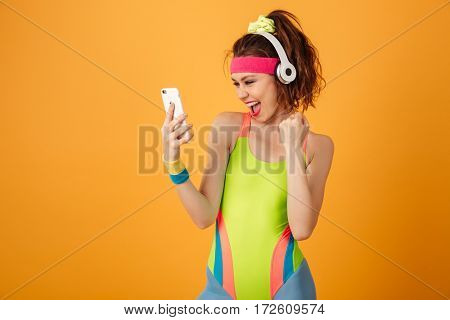Happy young fitness woman in earphones listening to music from smartphone over yellow background