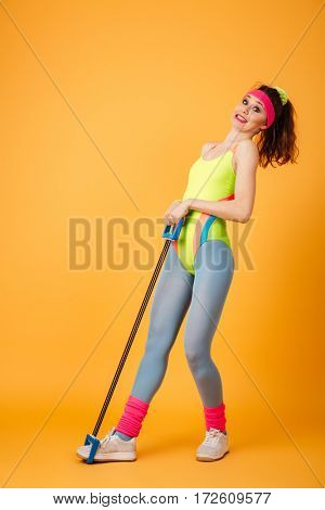 Full length of funny young sportswoman standing and stretching expander over yellow background