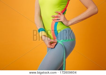 Closeup of slim fitness woman standing and using measuring tape over yellow background