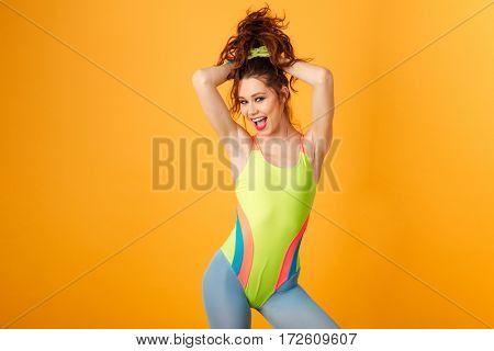 Cheerful beautiful young sportswoman standing and posing over yellow background