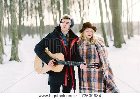 A man with a guitar holding hands with his girlfriend atmospheric sensual moment. Stylish hipster couple in trendy look. rustic wedding concept winter forest.