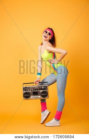 Full length of attractive young sportswoman standing and posing with retro boombox over yellow background