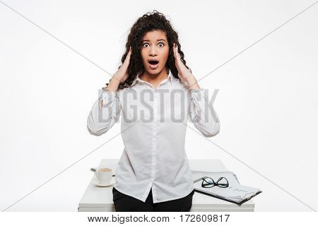 Picture of shocked african business lady standing near table over white background touching head. Looking at camera.