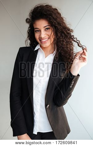 Photo of cute african businesswoman standing over grey background. Looking at camera.