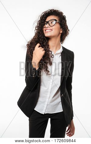 Image of pretty african business lady wearing glasses standing over white background. Looking aside.