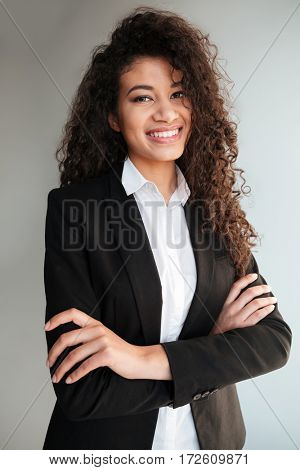 Photo of gorgeous african business lady standing with arms crossed over grey background. Looking at camera.