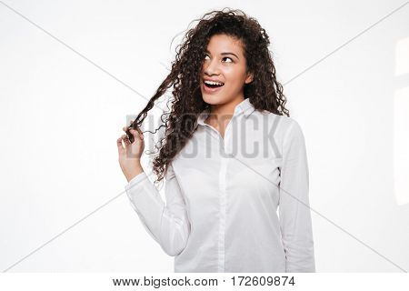 Picture of cheerful african businesswoman standing isolated over white background. Looking aside.
