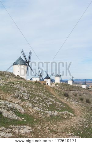 White old windmills on the hill near Consuegra (Castilla La Mancha Spain) a symbol of region and journeys of Don Quixote (Alonso Quijano) on cloudy day.
