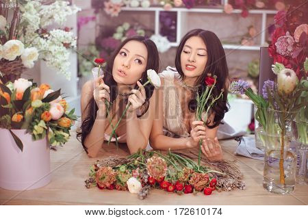 Beautiful asian florist girls making bouquet of flowers on table for sale against floral background in flower shop indoors. Two attractive asian females florists working in store. 2 playful fashion models in tender dresses posing playing with flowers.