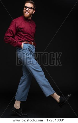 Vertical image of Male nerd in eyeglasses with arms in pocket