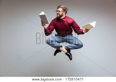 Male nerd jumping and reading in-flight. Isolated gray background
