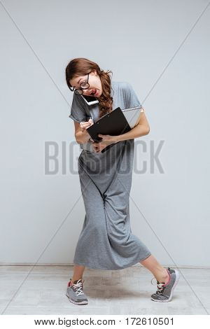 Vertical image of young clumsy female nerd in funny eyeglasses which talking on phone and holding laptop, notebook and clipboard
