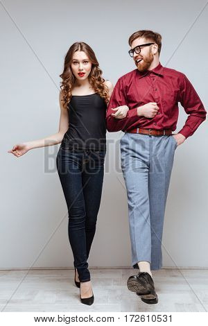 Vertical image of Sexy Woman holding hand of Happy Male nerd