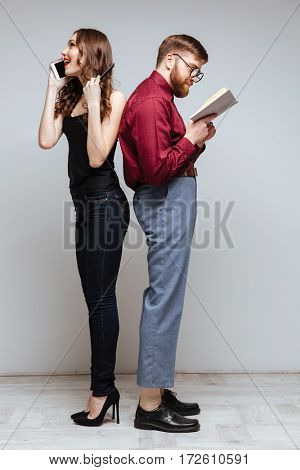 Woman and male nerd standing back each other while woman talking on phone and male nerd reading book