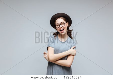 Happy Female nerd in eyeglasses and black hat with crossed arms and open mouth