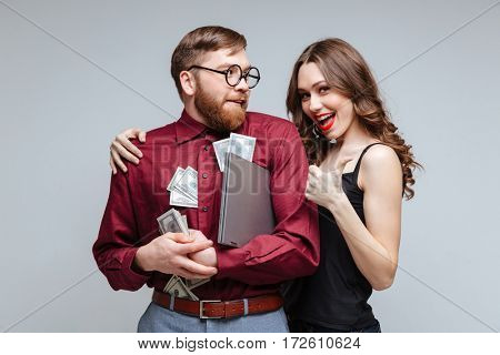 Happy Woman stick to Male nerd with money. Isolated gray background