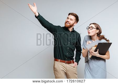 Bearded man showing something for Female nerd. Isolated gray background