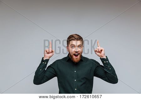 Happy Young Bearded man in green shirt and with open mouth pointing up