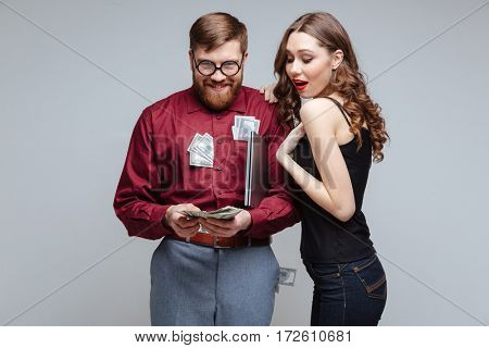 Cunning Male nerd holding many money and standing with interested girl