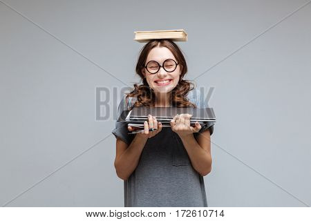 Smiling Female nerd in funny eyeglasses with book on head which holding laptop and notebook in hands