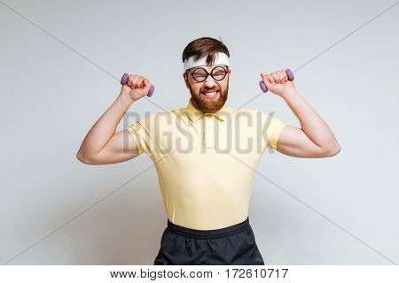 Male nerd in funny glasses and yellow shirt which training with light dumbbells