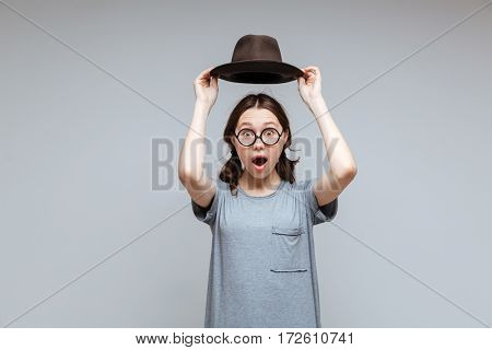 Surprised Female nerd holding overhead her hat with open mouth and looking at camera