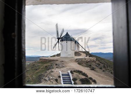 White old windmill on the hill near Consuegra (Castilla La Mancha Spain) a symbol of region and journeys of Don Quixote (Alonso Quijano) and a town on cloudy day a view through the window.