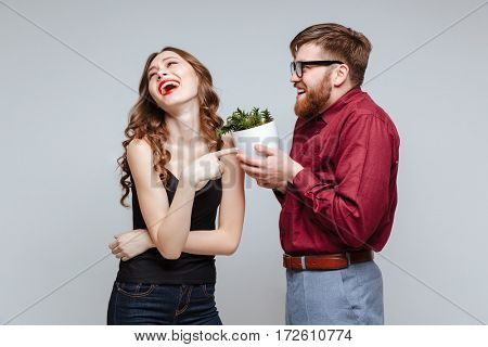 Male nerd presents the plant for laughing girl. Gray background