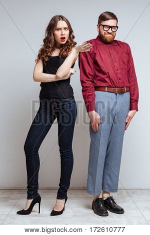 Vertical image of Pretty woman with Male nerd in funny eyeglasses