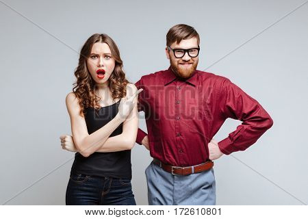 Shocked woman with smiling male nerd in funny clothes and eyeglasses