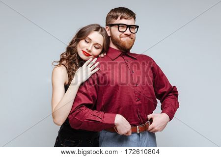 Pretty Woman lying on shoulder of Smiling Male nerd in eyeglasses and funny clothes