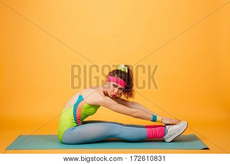 Photo of amazing young sports lady make sports exercises over yellow background. Looking at camera.