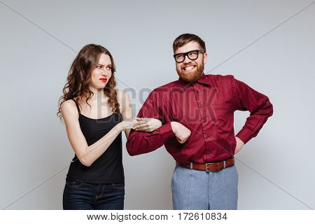 Displeased woman holding hand of Male nerd in funny clothes and eyeglasses