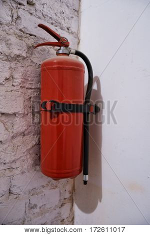 Red fire extinguisher hanging on a white brick wall