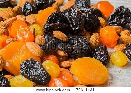 prunes, dried apricots, dried mandarins and almonds on a light wooden background.
